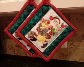 Santa and all his Gifts with Emerald Border and Red Trim Quilted Potholders or Hotpads Set