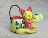 Halloween Candy Kitty Fairy - A bright yellow and magenta swirled fairy cat with pumpkin pail of candy