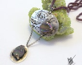 Silver pendant with titanium agate druzy and beaded rope.