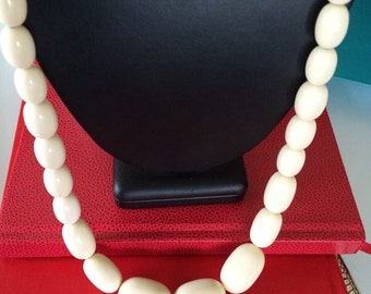 Large long strand of bone colored oval graduated beads