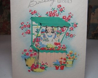 Sweet 1944 die cut embossed birthday greeting card pretty lady selling flowers at a flower stand with a bluebird in cage