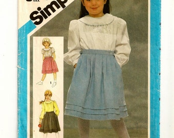 "A Pleated Wrap Skirt & Long or Short Sleeve Blouse Sewing Pattern with Collar Variations: Uncut - Girls Size 6, Breast 25"" • Simplicity 6558"