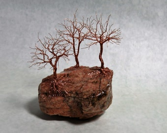 Three bare-branch trees on a granite rock - a recycled copper wire tree sculpture.