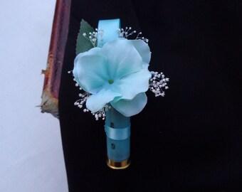 Boutonniere designed in a spent shotgun shell in aqua-tropical blue