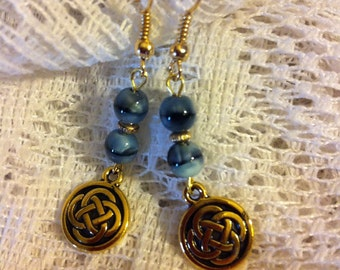 Blue cats eye and gold plated pierced earrings with Celtic knot charms.