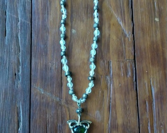 White glass beads from Italy, mixed with metal beads. Dark green crystal at bottom.  One of a kind.