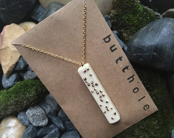 "Braille necklace in ""butthole"""