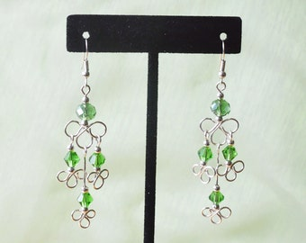 Clover leaf chandelier earrings with green crystals.