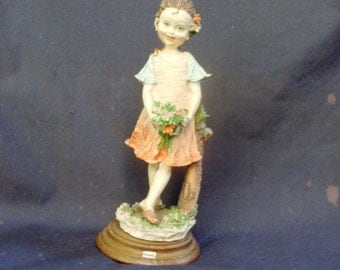 statua di bambina, statue of a little girl gathering flowers in the woods, leaning against the trunk of a tree, a smile in his cheeks pink
