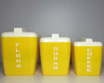 set of three yellow and white plastic nesting canisters