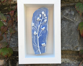 Rustic clay wall art, impression of natural blackberry buds, blue and white, in a white wooden box frame.