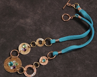 Baubles and Bling mixed media necklace: hammered copper, brass, bronze discs, washers, Swarovski crystal, turquoise leather