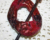 Red shawl pin with black and copper accents