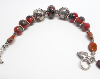 Large Sterling silver beads with large artist  lampwork beads in orangish and Browns makes for a substantial bracelet w/dangles and toogle