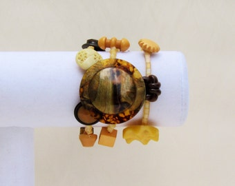 Handmade button bracelet with earth tone celluloid, bakelite, plastic and vegetable ivory buttons and gold cube beads, memory wire bracelet
