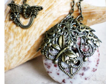 Crazy lace agate pendant, a round donut stone adorned with bronze filigree and dragonfly.