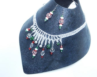Crocheted statement necklace in white and metallic silver thread and red, green and crystal beads. Comes with matching earrings