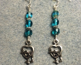 Silver dolphins in a heart charm dangle earrings adorned with turquoise Czech glass beads.
