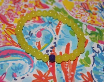 Yellow beaded bracelet accented with purple bead