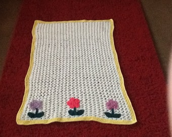 Hand crochet white baby blanket embellished with crochet flowers