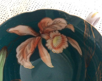 Vintage Japanese Osaku tea cup saucer in black  gold dark jade green with orange coral orchids and gold trim.