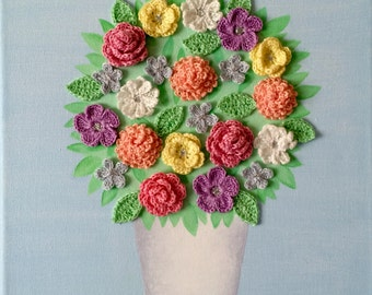 Pretty pastel wall art painted in acrylic paint with crocheted flowers and a touch of glitter.