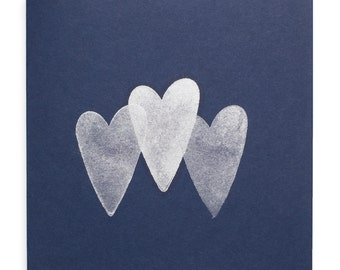Handmade greeting card in blue featuring three elegant silver hearts