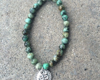 African turquoise stretch bracelet with silver ohm charm