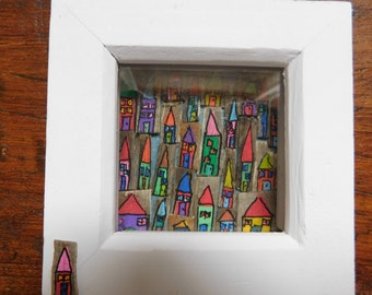 Hand painted drift wood houses in a frame.