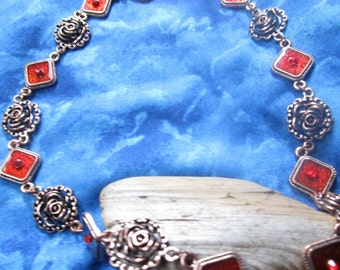Copper colored roses and red triangles with red rhinestones, what a necklace!
