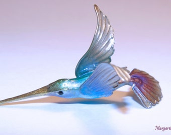 A small hummingbird. Brooch / Hairpin. For example.