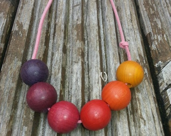 Vintage wooden necklace on pink suede