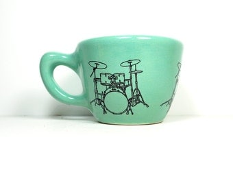 12oz cup glazed in Blue Green, with a drumkit print. Made to Order / Pick Your Colour