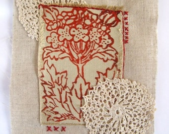 Small textile art quilt / applique. Vintage lace doily, hand embroidery and floral print on fabric red / neutral