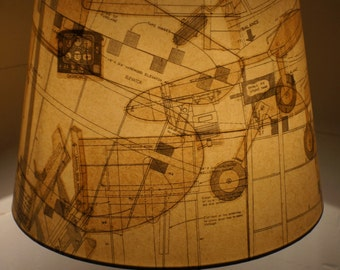 Unique lamp shade covered in vintage model aircraft plans gives a warm conversational glow