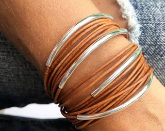 brown leather bracelet triple wrap with silver bangle accents. Lobster clasp chain closure. Fall fashion trends jewelry.