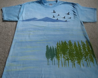 Birds flying above the mountain tops along the Inland Passage Way, fir trees in greens, man's medium dyed & screen printed t-shirt, blues