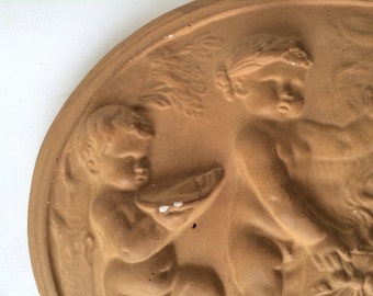 A medaillon with putti from a serie of 4. Painted plaster.1930