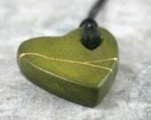 Olive green faux kintsugi (kintsukuroi) broken heart pendant with gold repair in bisque porcelain on black cotton cord - OOAK