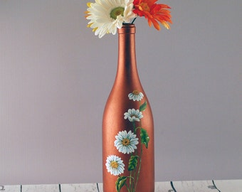 Hand painted wine bottle vase featuring white daisies on a dark copper-colored background