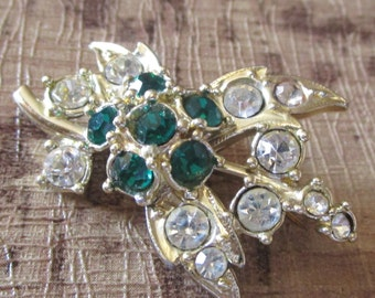 "intage silvertone brooch with deep green stones/clear stones 1.5""high x 1""in good condition for age"