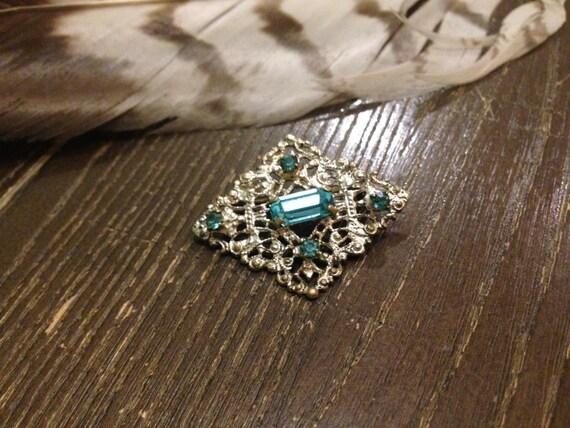 Silver colored, Diamond-shaped figure vintage brooch, with light blue rhinestones