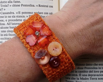 Orange textile fabric bracelet whit buttons and flower velcro fastening