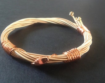 A handmade bronze acoustic recycled guitar string bracelet/bangle with a bronze bead.
