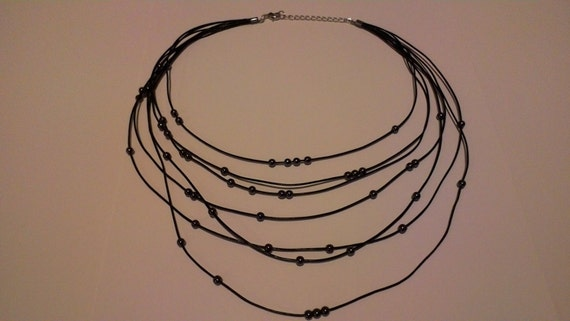 necklace made of black leather cord and gray or silver hematite beads