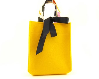 Small bright yellow wool felt bag with patterned handles and navy grosgrain ribbon bow