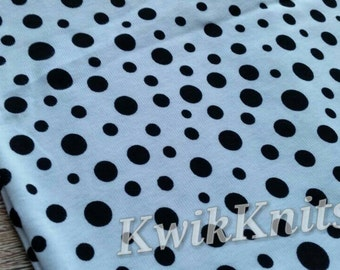 Small black spots on white cotton rib knit fabric