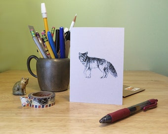 Coyote note card. Black line drawing of a coyote, blank inside with text on the back about coyote the trickster.