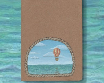 Hot Air Balloon journal or notebook. An original painting of a balloon floating through the sky, above the sea, on the cover of a blank book