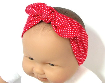 Red baby headband with white dots, elastic at the back, ajustable with the knot